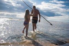 有她的父亲的女孩进来海的波浪 免版税库存图片