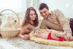 有她的父母的赤裸婴孩 免版税库存照片