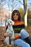 有她的狗的一个女孩在五颜六色的秋天森林里 库存照片
