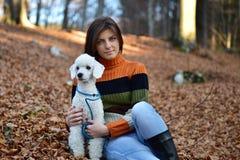 有她的狗的一个女孩在五颜六色的秋天森林里 图库摄影