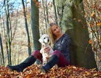 有她的狗的一个女孩在五颜六色的秋天 图库摄影
