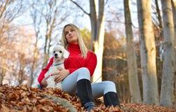 有她的狗的一个女孩在五颜六色的秋天 库存照片