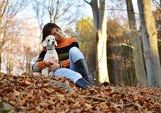 有她的狗的一个女孩在五颜六色的秋天 免版税库存照片