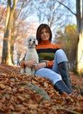有她的狗的一个女孩在五颜六色的秋天 免版税库存图片