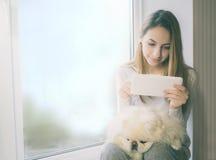 有她的狗的女孩在家坐窗台和用途片剂个人计算机 库存图片