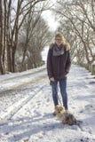 有她的狗的女孩在雪 免版税库存图片
