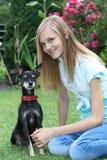 有她的狗的微笑的十几岁的女孩 免版税图库摄影