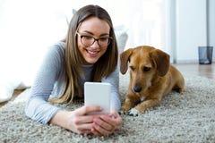 有她的狗的美丽的少妇使用手机在家 免版税库存照片