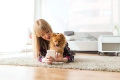 有她的狗的美丽的少妇使用手机在家 免版税库存图片