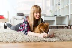 有她的狗的美丽的少妇使用手机在家 库存图片