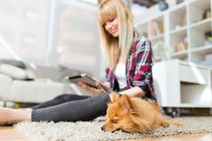 有她的狗的美丽的少妇使用数字式片剂在家 免版税库存照片