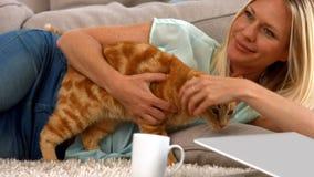 有她的猫的愉快的金发碧眼的女人 股票视频