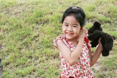 有她的玩偶的女孩在庭院里 免版税图库摄影