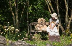 有她的玩具熊的小逗人喜爱的女孩坐一个长木凳我 免版税库存图片
