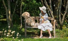 有她的玩具熊的小逗人喜爱的女孩坐一个长木凳我 免版税图库摄影