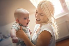 有她的男婴的愉快的母亲胳膊的 免版税库存图片
