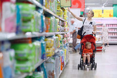 有她的男孩的母亲在超级市场 免版税库存图片