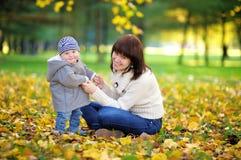 有她的男婴的年轻母亲在秋天公园 免版税库存图片
