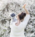 有她的白色狮子狗的妇女在春天庭院里 免版税库存照片