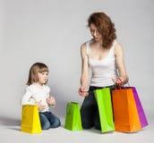 有她的看起来里面购物袋的母亲的小女孩 免版税库存照片