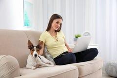 有她的研究膝上型计算机的狗的美女 免版税库存照片