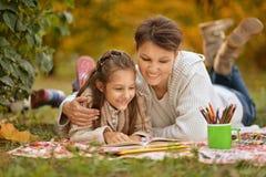 有她的祖母读书的女孩 免版税图库摄影