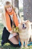 有她的穿温暖的衣裳的狗的可爱的女孩 图库摄影