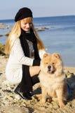 有她的穿温暖的衣裳的狗的可爱的女孩 库存图片