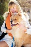 有她的穿温暖的衣裳的狗的可爱的女孩 免版税库存照片