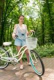 有她的站立在一条小径的自行车的年轻女性在公园 免版税库存图片
