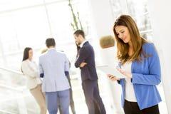 有她的站立在办公室的片剂的女实业家 免版税库存照片
