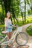 有她的站立在小径的自行车的美丽的少妇  免版税库存图片