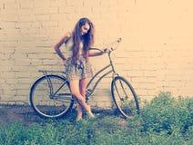 有她的站立在白色墙壁附近和注视着下来脚的都市自行车的哀伤的女孩,减速火箭的看的instagram定了调子射击 库存照片
