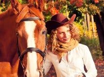 有她的红色马的愉快的女牛仔。 库存照片