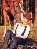 有她的红色马的美丽的女牛仔 免版税库存照片