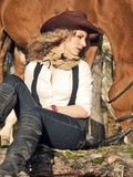 有她的红色马的逗人喜爱的女牛仔。 库存图片