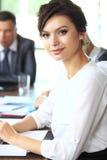 有她的职员的女商人,人小组在背景中 免版税图库摄影