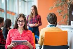 有她的职员的愉快的年轻女商人,人小组在背景中在现代明亮的办公室户内 免版税库存图片