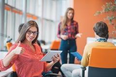 有她的职员的愉快的年轻女商人,人小组在背景中在现代明亮的办公室户内 库存图片