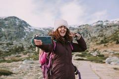 有她的背包和一个帽子的深色的女孩在她的头她在与大微笑的山旁边拍照片在她的嘴 免版税库存照片
