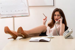 有她的腿的女商人在桌上 免版税库存照片