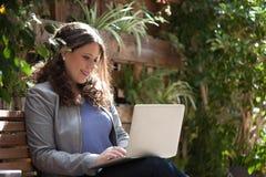 有她的膝上型计算机的愉快的女商人在街道的长凳 免版税库存照片