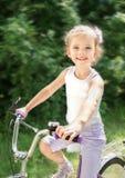 有她的自行车的微笑的逗人喜爱的小女孩 免版税图库摄影