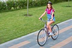 有她的自行车的美丽的少妇在公园 免版税图库摄影