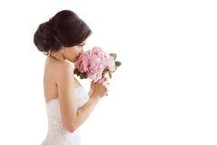 有她的花的美丽的新娘 婚礼发型构成豪华时尚礼服和花束 免版税库存照片