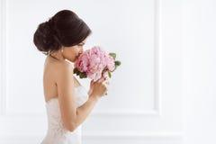 有她的花的美丽的新娘 婚礼发型构成豪华时尚礼服和花束 免版税库存图片