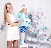 有她的装饰圣诞树的妈妈的逗人喜爱的小女孩 免版税图库摄影