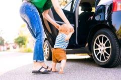 有她的走乘汽车的小男婴的年轻母亲 库存照片