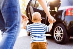有她的走乘汽车的小男婴的年轻母亲 免版税图库摄影