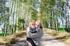 有她的走户外在秋天公园的小小女儿的年轻母亲 免版税库存图片